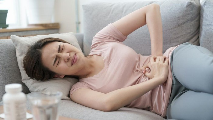 asian woman with menstruation and pain period cramps. young women having painful sleeping on sofa at her home