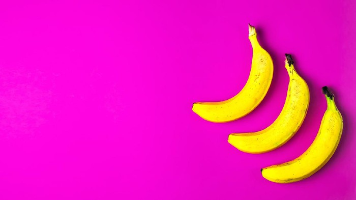 Three ripe yellow bananas on a bright red paper background. Flat lay, copy space, concept postcard or banner