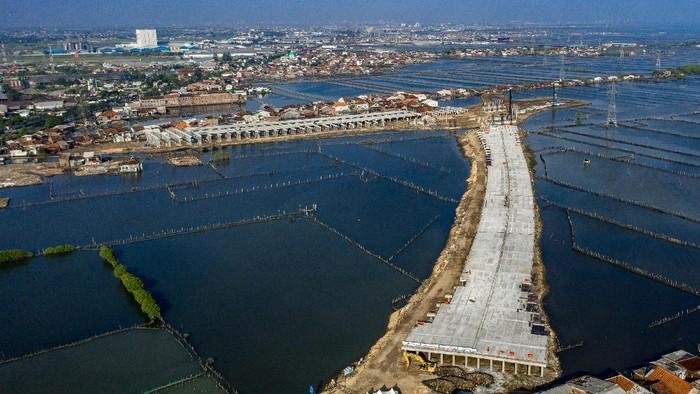Foto udara proyek pembangunan Jalan Tol Semarang - Demak seksi II di Kecamatan Sayung, Kabupaten Demak, Jawa Tengah, Selasa (13/4/2021). PT PP - Wika Join Operation selaku kontraktor pelaksana proyek senilai Rp15,3 triliun tersebut menargetkan penyelesaian jalan tol sepanjang 27 kilometer yang akan terintegrasi dengan tanggul laut itu pada Mei 2022 mendatang, hingga hari ini (13/4/2021)  progres pembangunannya telah mencapai sekitar 40 persen. ANTARA FOTO/Aji Styawan/hp.