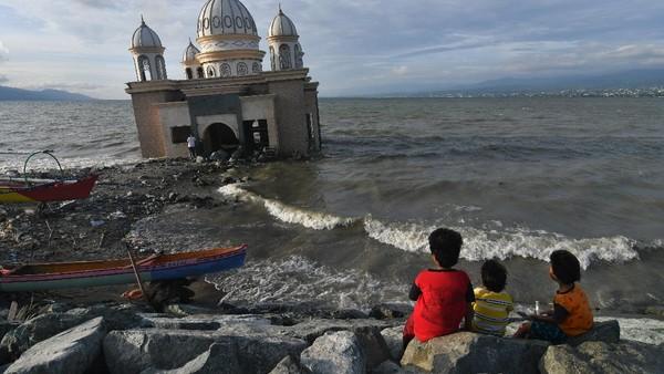 Warga menunggu datangnya waktu berbuka puasa (ngabuburit) di sekitar Masjid Terapung Arkam Babu Rahman yang rusak akibat diterjang tsunami di Pantai Teluk Palu di Palu, Sulawesi Tengah, Selasa (13/4/2021).
