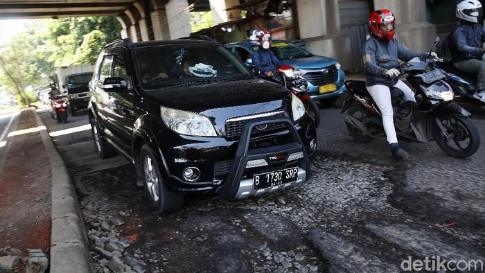 Pengendara mengindari jalan rusak di Jalan I Gusti Ngurah Rai Bekasi arah Jakarta depan Stasiun Cakung Kota Bekasi, Jawa Barat, Rabu (14/4/2021). Jalan rusak dikawasan ini sudah berlangsung beberapa bulan akibat buruknya drainase dan terandam genangan saat hujan.