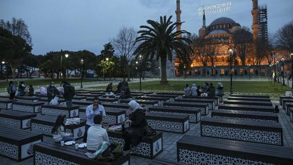 Orang-orang berbuka puasa dengan latar belakang Masjid Sultan Ahmed atau lebih dikenal sebagai Masjid Biru di Istanbul, Turki, Selasa (13/4/2021) waktu setempat.