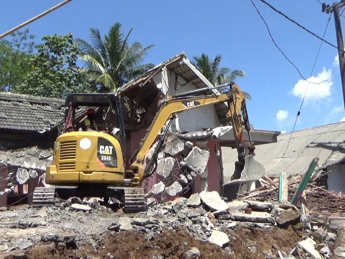 Pembersihan puing bangunan rumah warga yang rusak akibat gempa magnitudo 6,1, terus dilakukan. Satu unit alat berat dikerahkan ke desa Kali Uling, Kecamatan Tempursari, Lumajang.