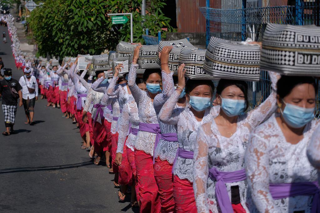 Umat Hindu mengusung keben bambu atau tempat sesajen dalam tradisi Mapeed yaitu rangkaian persembahyangan Hari Raya Galungan di Desa Lukluk, Badung, Bali, Rabu (14/4/2021). Tradisi yang biasanya berjalan beriringan dengan menjunjung gebogan atau sesajen bersusun buah, bunga dan hiasan janur tersebut digelar secara sederhana untuk menekan pengeluaran bagi warga di masa pandemi COVID-19. ANTARA FOTO/Nyoman Hendra Wibowo/hp.
