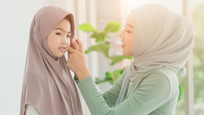 Muslim or Islam mother dressing hijab for her daughter at home in the morning.
