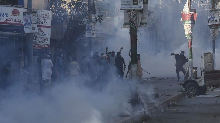 Police personnel use teargas shell to disperse supporters of Tehreek-e-Labbaik Pakistan (TLP) party during a protest against the arrest of their leader as he was demanding the expulsion of the French ambassador over depictions of Prophet Muhammad, in Karachi on April 13, 2021. (Photo by Asif HASSAN / AFP)
