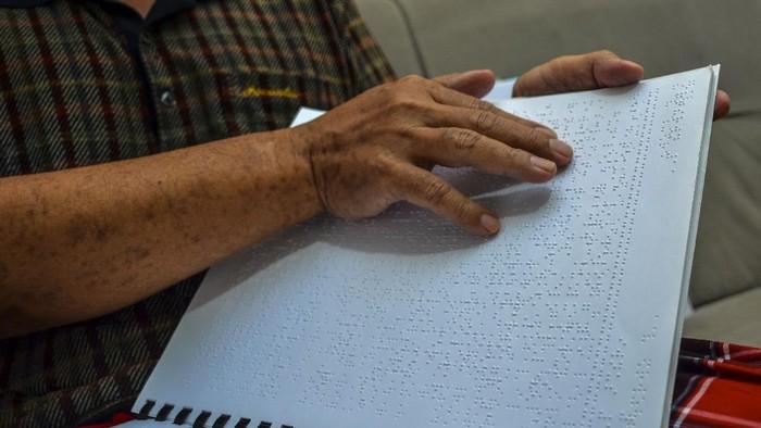 Seorang penyandang tunanetra membaca Al-Quran braille di Kampung Cintarasa, Kota Tasikmalaya, Jawa Barat, Rabu (14/4/2021). Di tengah pandemi COVID-19, bulan suci Ramadhan tahun ini Majelis Taklim Al Hikmah Penyandang Disabilitas mengadakan tadarus secara daring dengan cara saling berkirim voice note atau pesan suara ke dalam grup aplikasi telegram yang diikuti secara serentak oleh para jemaah dari seluruh Indonesia. ANTARA FOTO/Adeng Bustomi/hp.