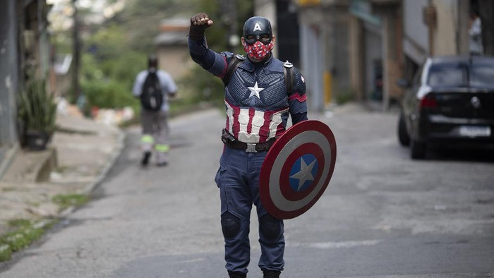 Military police offcier Everaldo Pinto, dressed as superhero Captain America, rides his motorcycle amid the COVID-19 pandemic in Petropolis, Rio de Janeiro state, Brazil, Thursday, April 15, 2021. Using his own resources, Pinto advises children on the need to protect themselves against COVID-19, distributing kits equipped with cleaning products and protective face masks to prevent the spread of the new coronavirus. (AP Photo/Silvia Izquierdo)