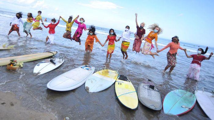 Peselancar wanita yang mengenakan busana kebaya berselancar di Pantai Kuta, Badung, Bali, Jumat (16/4/2021). Kegiatan yang diikuti puluhan perempuan termasuk sejumlah WNA tersebut dilakukan untuk menyambut peringatan Hari Kartini serta membangkitkan sektor pariwisata Bali yang terdampak pandemi COVID-19. ANTARA FOTO/Fikri Yusuf/wsj.