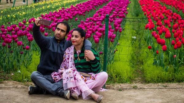 Pengunjung berbondong-bondong untuk menyaksikan bunga tulip yang sedang mekar di taman kawasan Zabarwan, Srinagar, India.