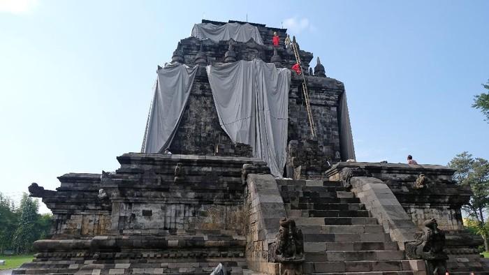 Petugas Balai Konservasi Borobudur (BKB) melepas terpaulin penutup Candi Mendut di Mendut, Mungkid, Magelang, Jawa Tengah, Jumat (16/4/2021). Setelah ditutup selama enam bulan untuk mengantisipasi paparan abu vulkanik Gunung Merapi, petugas BKB bersama masyarakat pariwisata membuka terpaulin penutup Candi Mendut karena menurut Badan Penyelidikan dan Pengembangan Teknologi Kebencanaan Geologi (BPPTKG) Yogyakarta, Candi Mendut aman dari ancaman bahaya erupsi Gunung Merapi. ANTARA FOTO/Anis Efizudin/wsj.
