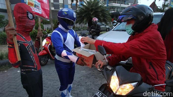 Sejumlah superhero mulai dari power rangers, spiderman hingga super girl terlihat membagikan takjil gratis di perempatan Patung Pandawa, Sukoharjo.