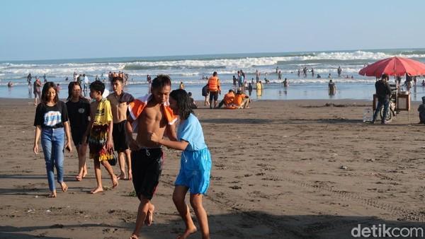 Dari pantauan detikTravel, tampak beberapa orang wisatawan tanpa mengenakan masker tengah bermain air dengan riang gembira. Sedangkan wisatawan yang duduk di pinggir pantai sebagian besar tidak mengenakan masker. (Pradito Rida Pertana/detikTravel)