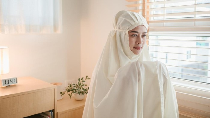 Young muslim woman in beige hijab and traditional clothes praying for Allah at home