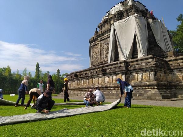 Beginilah situasi saat selimut terpaulin yang menutupi Candi Mendut dibuka. Selimut ini dibuka pada Jumat (16/4) ini oleh staff Balai Konservasi Borobudur (BKB) dibantu masyarakat setempat.
