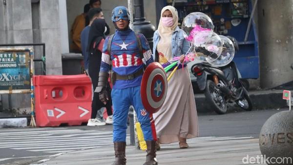 Ada juga cosplayer Captain America. Karena masih dalam situasi COVID-19, bagi Anda yang hendak ngabuburit di Jalan Asia Afrika atau kawasan Gedung Merdeka tetap menjaga protokol kesehatan. (Wisma Putra/detikTravel)
