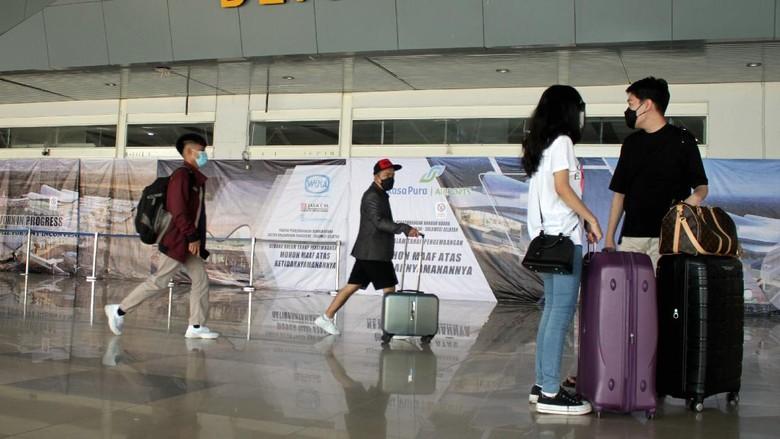 Sejumlah calon penumpang berjalan masuk ke dalam terminal keberangkatan di Bandara Internasional Sultan Hasanuddin, Maros, Sulawesi Selatan, Minggu (18/4/2021). Pihak bandara setempat mengaku telah siap mengantisipasi lonjakan penumpang jelang berlakunya pelarangan mudik oleh pemerintah pada 6-17 Mei 2021 dengan menerapkan protokol kesehatan COVID-19 secara ketat. ANTARA FOTO/Arnas Padda/yu/aww.