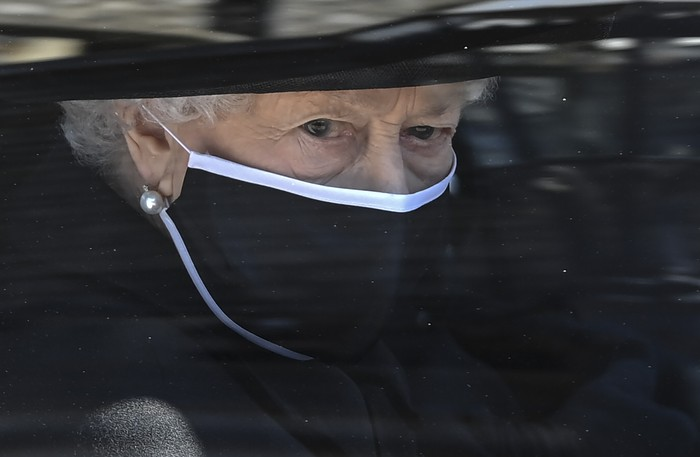 Britains Queen Elizabeth II follows the coffin in a car as it makes its way past the Round Tower during the funeral of Britains Prince Philip inside Windsor Castle in Windsor, England Saturday April 17, 2021. (Leon Neal/Pool via AP)