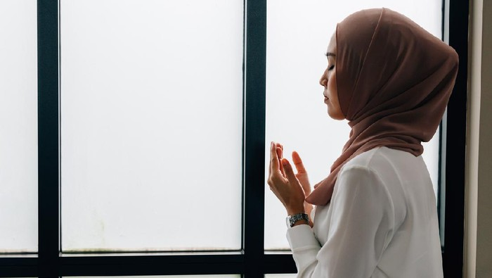 Southeast Asian Islamic female in hijab clasping hands and looking up while standing near window during prayer