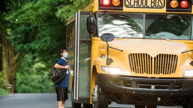 Young female bus driver driving he school bus, wearing a face mask. She is taking care that kids sit down.