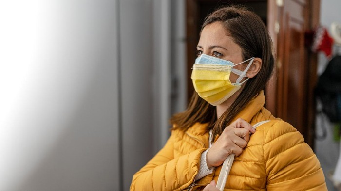 Young Woman wearing double face mask before going out