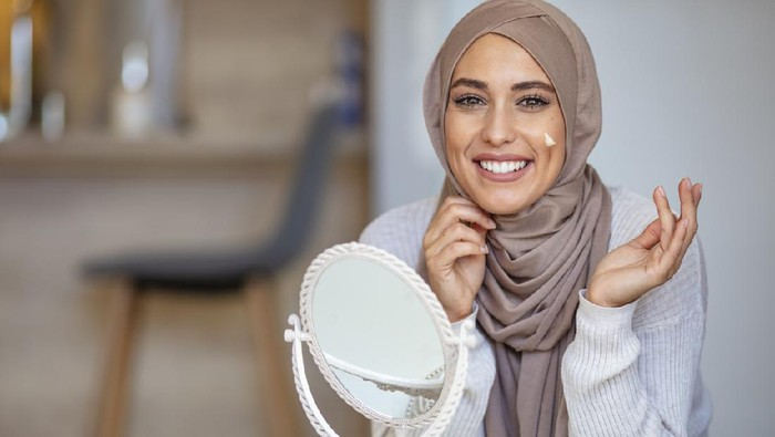 Muslim woman spreading cream over her face while looking in the mirror. Beauty treatment. Female putting on moisturizer on her facial. Muslim woman applying cream to face and looking to mirror