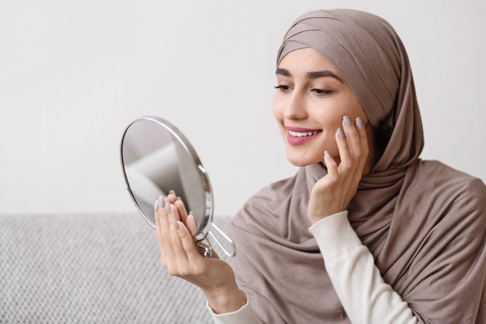 Beauty routine. Attractive muslim girl in hijab holding mirror and looking at her face with perfect soft skin, sitting on sofa at home, free space