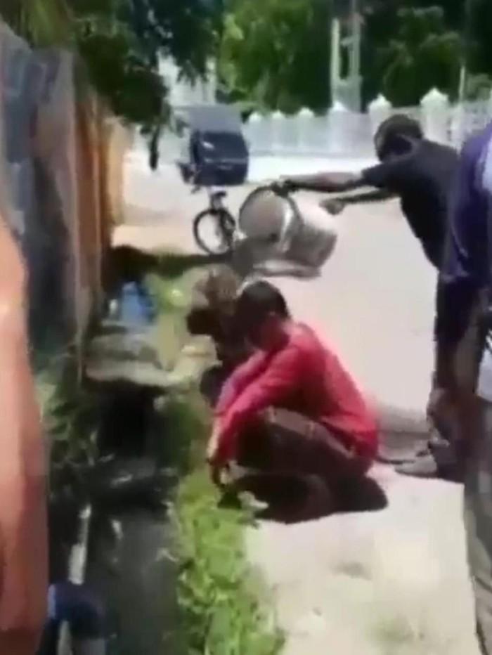 Pasangan selingkuh di Banda Aceh, Aceh berinisial HAM dan perempuan FA digerebek warga berduaan di kosan. Mereka sempat dimandikan air comberan (Screenshot video viral)