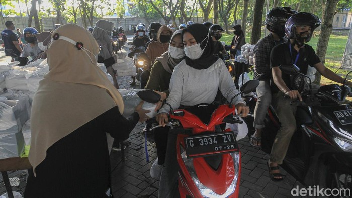 Petugas membagikan paket takjil gratis kepada mahasiswa Universitas Muhammadiyah Yogyakarta (UMY)  di komplek Universitas Muhammadiyah Yogyakarta, Bantul, Yogyakarta, Senin (19/4/2021).