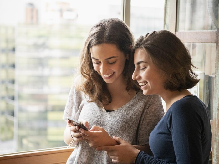 Two sisters laughing and looking at messages on cell phone, online, social media, texting