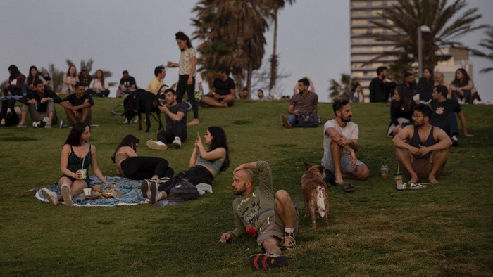 People without face masks watch the sunset, in Tel Aviv, Israel, Sunday, April 18, 2021. Israel has lifted a public mask mandate and fully reopened its education system in the latest easing of coronavirus restrictions following its mass vaccination drive. (AP Photo/Oded Balilty)