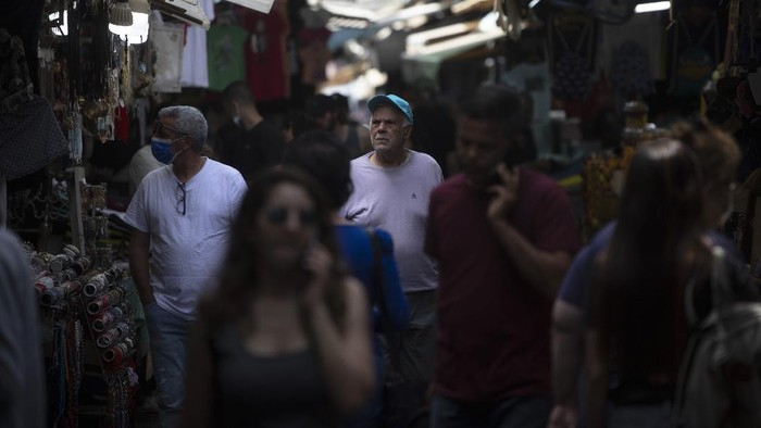 Israelis walk in a market in Tel Aviv, Israel, Sunday, April 18, 2021. Israel has lifted a public mask mandate and fully reopened its education system in the latest easing of coronavirus restrictions following its mass vaccination drive. (AP Photo/Sebastian Scheiner)