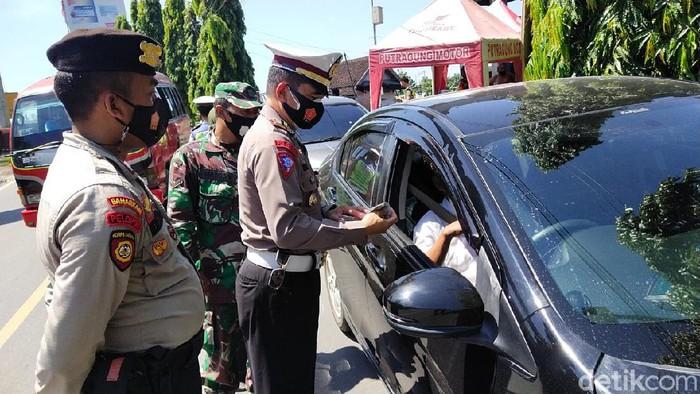Polisi mengecek pengendara yang melintas ke pintu masuk Jateng di Kabupaten Blora, Selasa (20/4/2021)