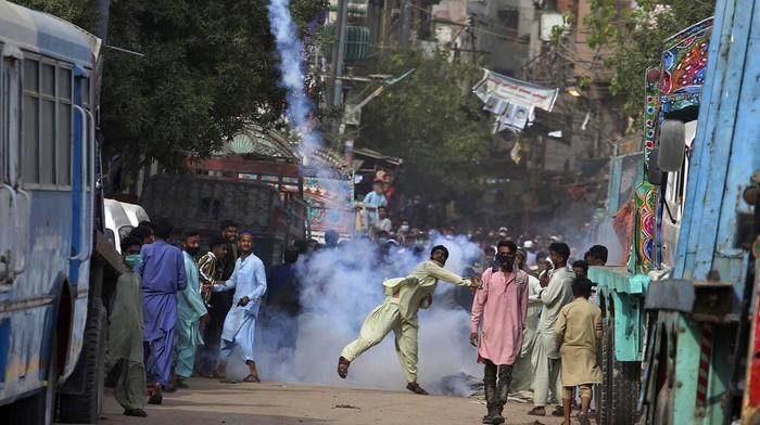 Bentrokan antara simpatisan Tehrik-e-Labaik Pakistan (TLP) dan polisi terjadi di Karachi, Pakistan, Senin (19/4/2021) waktu setempat. Dalam bentrokan itu sejumlah massa tampak melemparkan kembali tabung gas air mata yang ditembakkan polisi. AP Photo/Fareed Khan.
