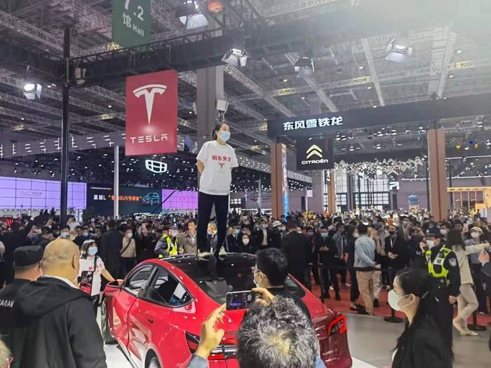 Wanita Ini Demo di Atas Mobil Display Tesla di Pameran, Protes Mobilnya Bermasalah