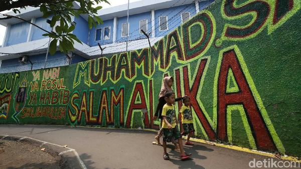 Warga berjalan di depan mural bernuansa Islami di Gang Pelangi, Kalibata, Jakarta Selatan, Rabu (21/4/2021).