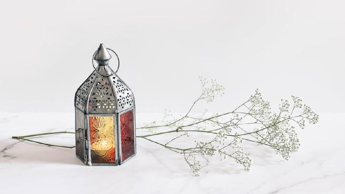 Burning silver vintage Moroccan, Arabic lantern. White gypsophila, babys breath flowers on marble table background, muslim holiday Ramadan Kareem greeting card, invitation. Empty copy space.