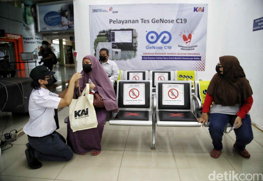 Petugas PT KAI Daop 1 memberikan bunga kepada penumpang kereta di kawasan Stasiun Gambir, Jakarta Pusat, Rabu (21/4).