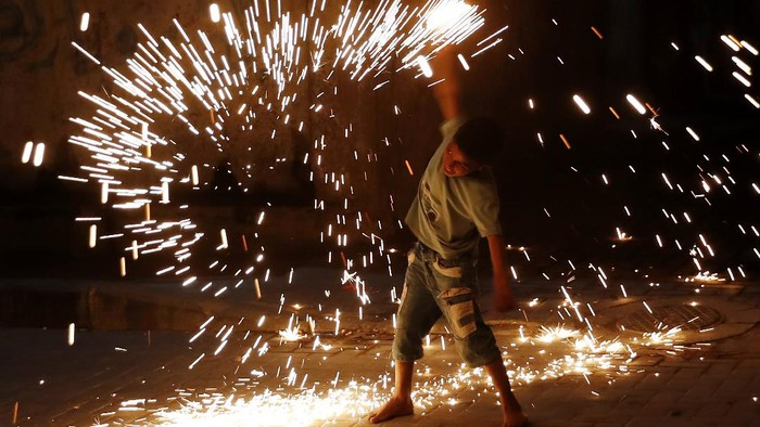 A young boy plays with fireworks as he celebrates during the Muslim holy fasting month of Ramadan along the alley in Gaza City, Tuesday, April 20, 2021. (AP Photo/Adel Hana)