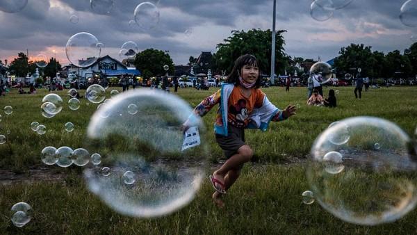 Seorang anak bermain dengan gelembung sabun saat umat Islam bersiap untuk berbuka puasa di Alun-alun Kidul, Yogyakarta.