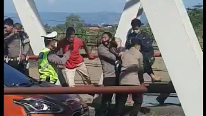 Tangkapan layar video viral penyelamatan wanita yang duduk di tepi jembatan Kudus