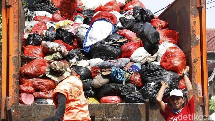 Pekerja membuang sampah ditempat pembuangan sampah sementara di kawasan Kampung Makasar, Jakarta Timur, Kamis (22/04/2021). Volume sampah pada bulan Ramadan 1442 Hijriah meningkat sebesar 20 persen dibandingkan hari biasa.