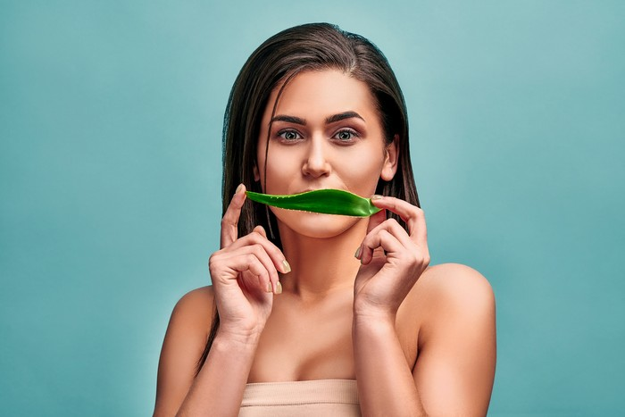 Portrait of a young beautiful woman who holds a leaf of aloe vera and hides a smile. The concept of cosmetics and facial and body care.