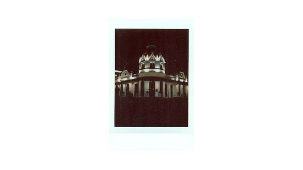 Penampakan Balai Pemuda saat dipotret dengan kamera instan di malam hari. Gedung Balai Pemuda diketahui dibangun pada tahun 1907 dan dijadikan sebagai pusat rekreasi bagi orang-orang Belanda di masa kolonial Hindia-Belanda. Tak jarang orang-orang Belanda datang ke gedung tersebut untuk menghadiri pesta, berdansa maupun bermain bowling. Bangunan yang dulu disebut De Simpangsche Societet ini dibangun Westmaes, salah seorang arsitek yang terkenal di Surabaya pada saat itu. Bentuk kubah sebagai atap adalah ciri aliran gothic. Gevel dan bracket yang membungkus kubah tersebut adalah warisan gaya vernakuler Belanda, sedangkan alur horizontal pada dinding kerap muncul pada aliran Renaissance. Wetmaes rupanya memilih gaya eklektisme untuk merancang bangunan Simpangsche Societeit ini.
