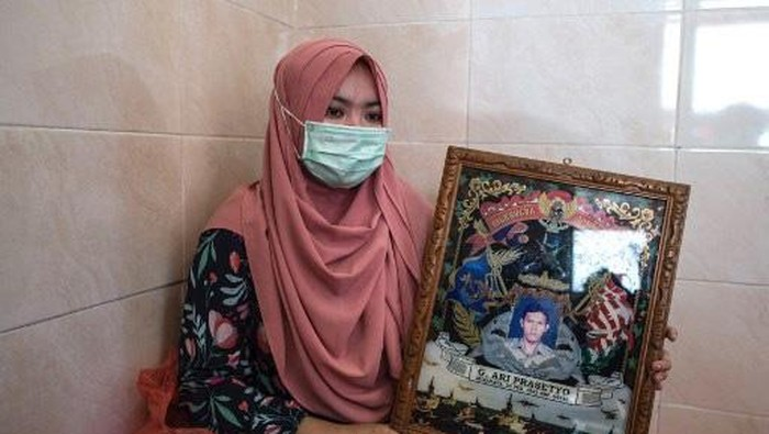 Berda Asmara talks about her sailor husband Mes Guntur Ari Prasetyo at their home in Surabaya on April 23, 2021, as the search continued for an Indonesian navy submarine with 53 crew aboard that went missing off the coast of Bali during training exercises on April 21. (Photo by Juni Kriswanto / AFP)