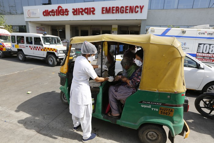 A COVID-19 patient attended inside a vehicle at a dedicated COVID-19 government hospital in Ahmedabad, India, Thursday, April 22, 2021. A fire killed 13 COVID-19 patients in a hospital in western India early Friday as an extreme surge in coronavirus infections leaves the nation short of medical care and oxygen. India reported another global record in daily infections for a second straight day Friday, adding 332,730 new cases. The surge already has driven its fragile health systems to the breaking point with understaffed hospitals overflowing with patients and critically short of supplies. (AP Photo/Ajit Solanki)