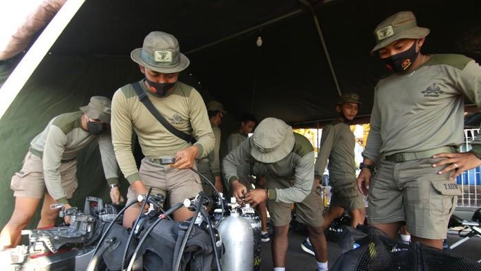 Prajuri dari satuan Yon Taifib 2 Marinir TNI AL mengecek peralatan komunikasi di Pelabuhan Tanjung Wangi, Banyuwangi, Jawa Timur, Sabtu (24/4/2021). Sebanyak 28 personel Taifib disiagakan dalam pencarian Kapal Selam KRI Nanggala-402 yang hilang kontak saat menggelar latihan penembakan di utara Bali. FOTO/Budi Candra Setya/hp.