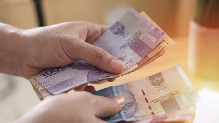 Close up of a person counting money, Uang Indonesian rupiah, cash in hand concept