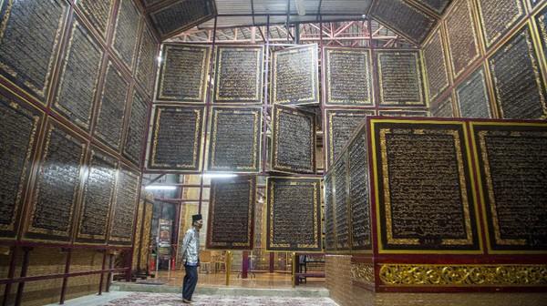 Ayat-ayat suci Alquran diukir di atas kayu trembesi.