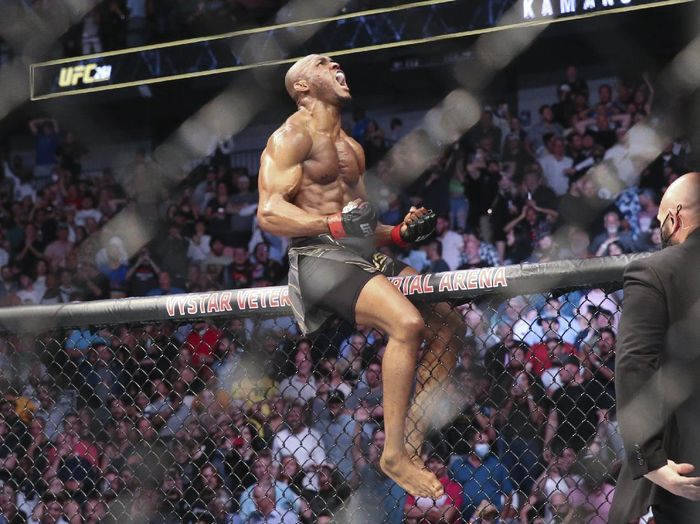 Kamaru Usman celebrates his win atop the octagon fence after a UFC 261 mixed martial arts bout against Jorge Masvidal early Sunday, April 25, 2021, in Jacksonville, Fla. (AP Photo/Gary McCullough)